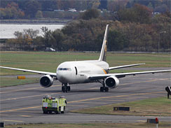 A jet lands near a United Parcel Service jet that is seen isolated on a runway at Philadelphia International Airport in Philadelphia, Friday, Oct. 29, 2010.