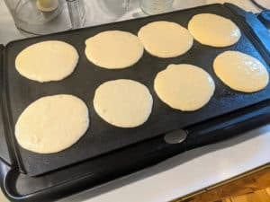 8 pancakes cooking on a griddle on white countertop