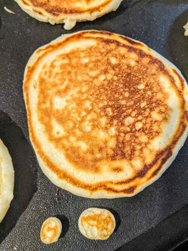 crisp, golden baby pancakes cooking on a griddle