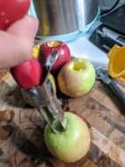hand on apple corer pressing into an apple on wood cutting board next to other cored apples and zester and juicer with scale and instant pot in the background