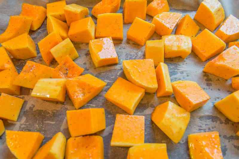 large diced butternut squash tossed in olive oil salt and pepper laid out on parchment paper in a sheet pan