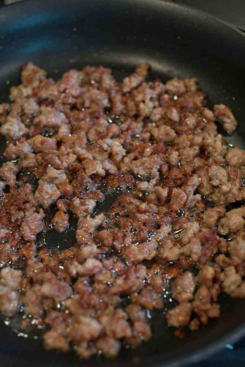 browned sausage bits cooking in a nonstick pan on the stove