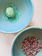 One blue bowl filled with green sugar sprinkles with a cookie dough ball, and another blue bowl filled with red, green, and white round sprinkles