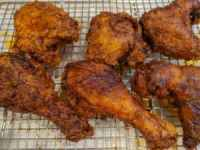 Nashville hot fried chicken rubbed in hot spicy oil cooling on a wire rack