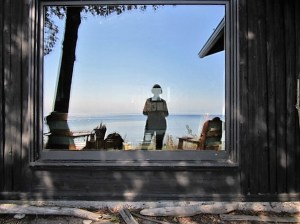 The author reflected in the window of her cottage.