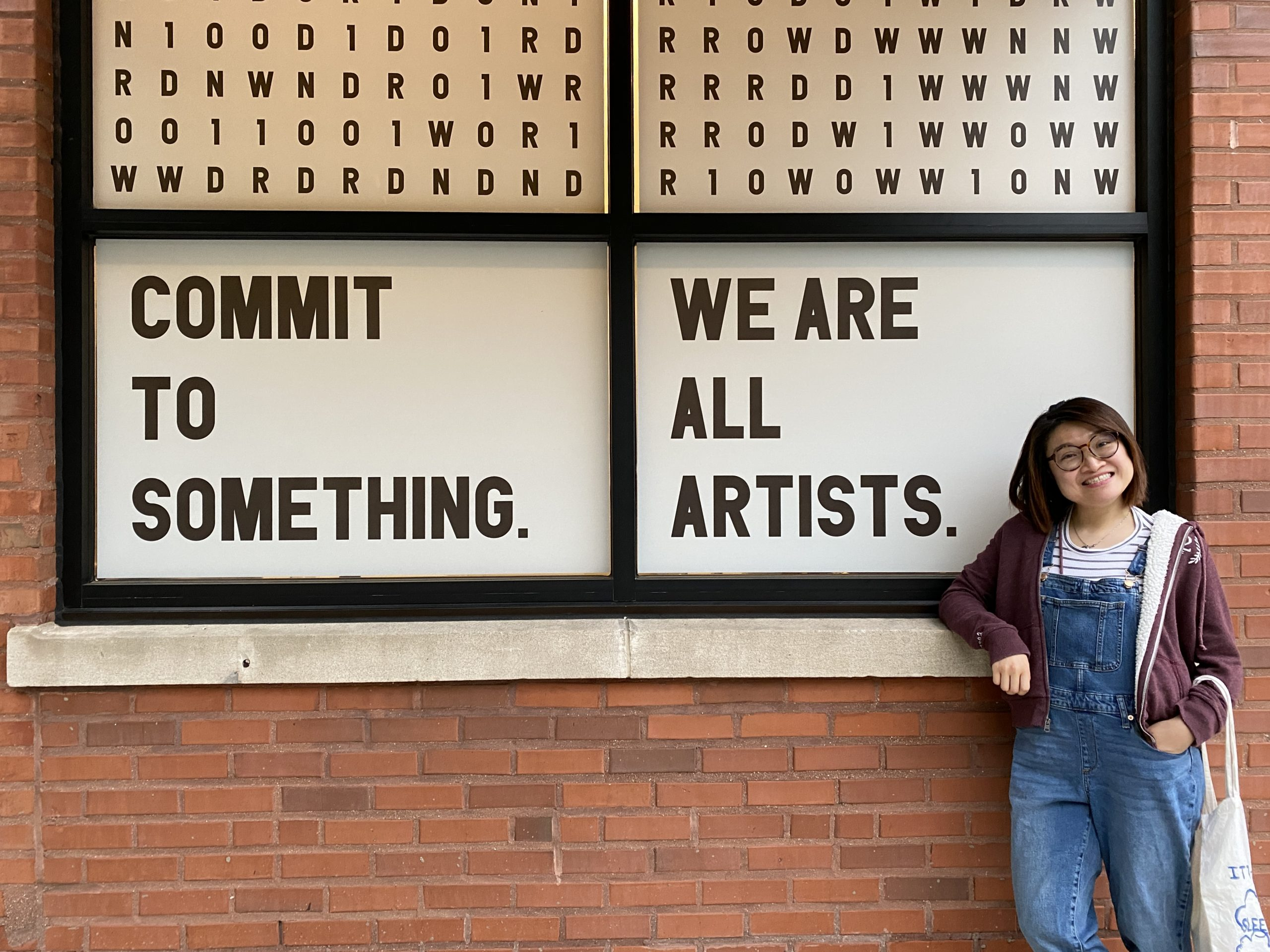 """Wenhao standing in front of the WNDR museum in Chicago. Windows behind her have signs saying """"Commit to something. We are all artists."""""""