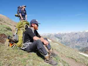 Joe Riis and Arthur Middleton rest while following an elk migration route. The elk cross several mountain passes, thwart predators and ford rivers moving between seasonal territories. Riis and Middleton are working on a documentary about the migration. (courtesy Jenny Nichols)