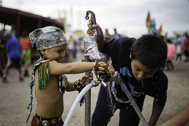 Kids play with water outside the dance arena to keep cool from the hot temperatures. Eastern Shoshone Indian Days, Fort Washakie, Wyoming. Sunday June 28, 2015 (Terance Oldman)