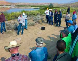Much of the landscape around Shell would be arid without irrigation, like that supplied by the existing Leavitt Reservoir behind participants in the Wyoming Water Develoopment Office tour last week. Jason Mead, deputy director for the dam and reservoirs section, addresses the group. (Angus M. Thuermer Jr./WyoFile)