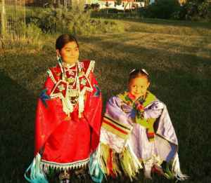 """Amarie Swallow (right) in her jingle dress. Children on the Wind River Indian Reservation face obstacles to health care, which can determine their """"life course."""" (photo by Matthew Copeland/WyoFile)"""