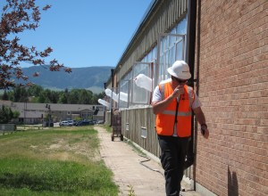 A worker at Kelly Walsh High School in Casper — which is undergoing a major expansion — dons personal protective wear. Several industries, including construction, have voluntarily formed safety programs with the state of Wyoming. (Dustin Bleizeffer/WyoFile)