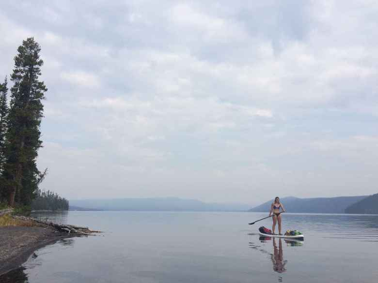 Alicia Maggard paddles on a hazy August morning on Shoshone Lake, a backcountry lake in Yellowstone National Park. If you're going to tour the lake by paddleboard, go when it is warm and paddle when winds are calm. (Kelsey Dayton/WyoFile)