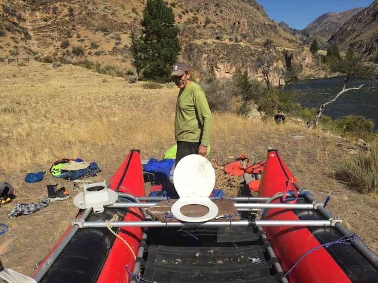 Dr. Bruce Hayse tries to figure out how to put together two halves of different catarafts at the start of the Middle Fork excursion. He also forgot the boat's seat, so fashioned one from materials at hand. (Brian Whitlock)