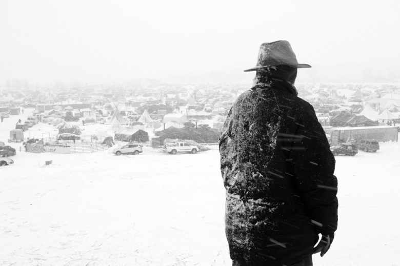 On Facebook Hill, the one place with cell reception, a reporter surveys the Oceti Sakowin Camp as a North Dakota blizzard moves in. The camp covered some 80 acres before a storm and frigid temperatures drove many residents away. (Angus M. Thuermer Jr./WyoFile)