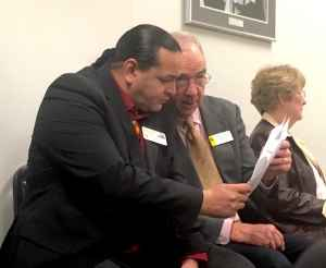 Jason Baldes, director of the Wind River Native Advocacy Center, confers with Rep. Jim Allen in a Senate committee room on Feb. 9. (Andrew Graham/WyoFile)
