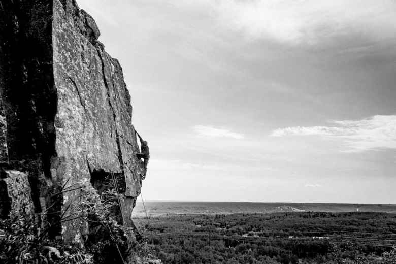 A climber makes his way up a rock face near Duluth, Minnesota. Duluth collapsed economically in the late 20th Century. The town reinvented itself over the past decade as a place known for recreation. (Hansi Johnson)