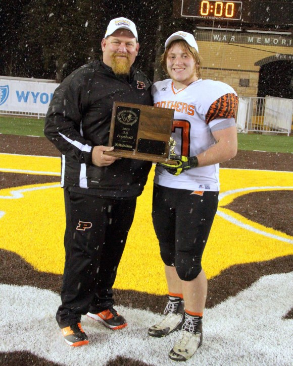 Stringer, with his son Riley, celebrates the Panthers' victory in the 2013 Class 3A title game. Photo courtesy Greg Wise.
