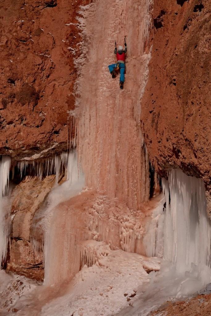 Kaitlin Dooling climbs the red-streaked ice of Ten Sleep Falls in lower Ten Sleep Canyon, Wyoming