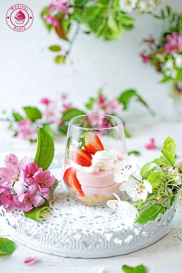 zdjęcie przedstawia sernik rabarbarowy w szklance przykładowe zdjęcie do zrobienia podczas kursu fotografii kulinarnej