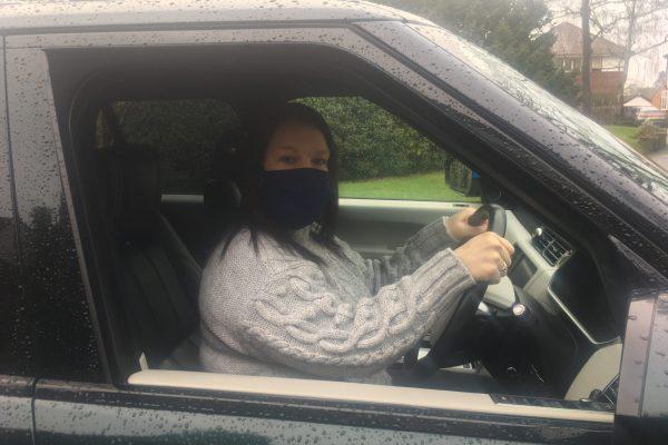 woman behind wheel wearing mask