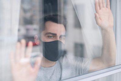 muzhchina-v-maske-vozle-okna-foto