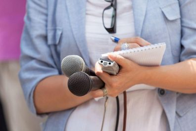 midsection-of-journalist-writing-in-notepad-while-holding-microphones-688987751-5a60e6879802070036b573a7