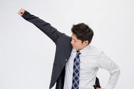 スーツに袖を通す男性