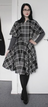 Striped long sleeved V-neck top. Matching black and white plaid full circle skirt and cape.