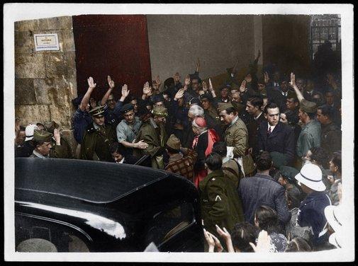 Momento en el que el escritor sale del acto acompañado de Carmen Polo de Franco -entrando en el coche- y Millán Astray. FOTO RESTAURADA Y COLOREADA POR RAFAEL NAVARRETE / ORIGINAL: MINISTERIO DEL INTERIOR / SECCIÓN TÉCNICA