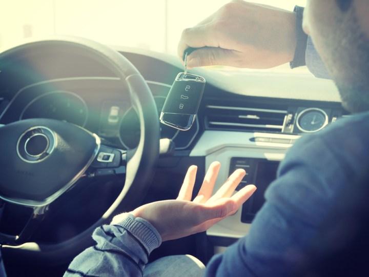Man handing over car keys to rental car driver
