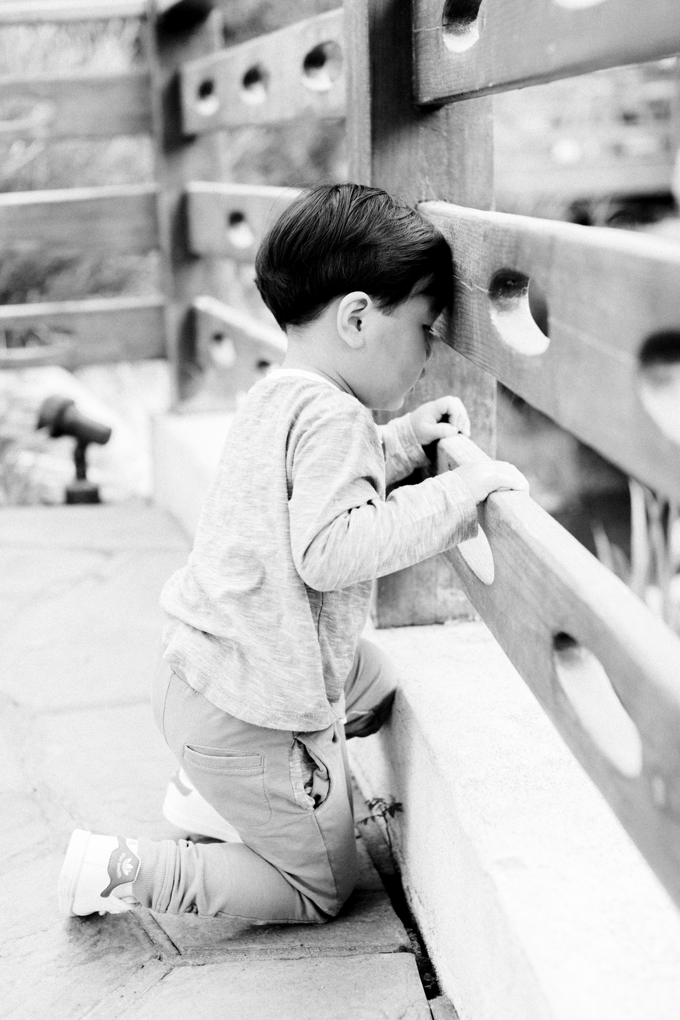 A young boy looking through the slats of a bridge during their family photography session in Cal Poly.