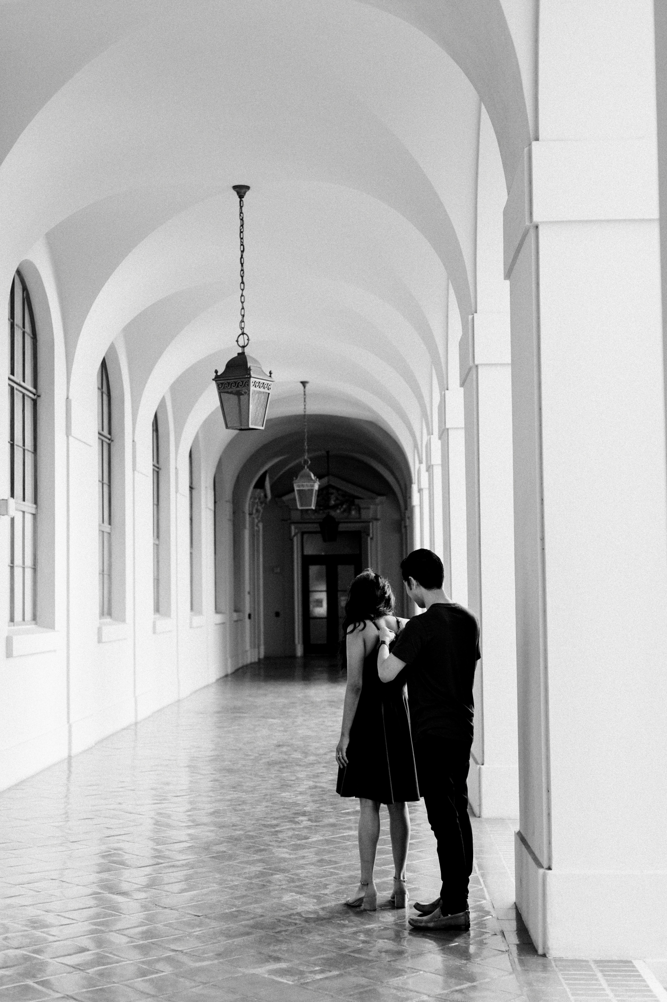 A man helping his fiance with her dress in Pasadena City Hall.