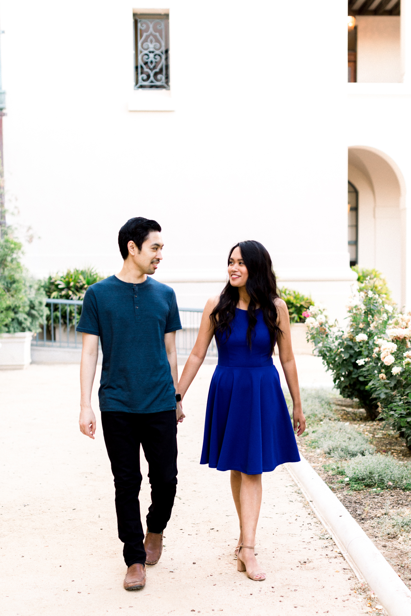 A couple walking together and looking at each other during their engagement photo session.