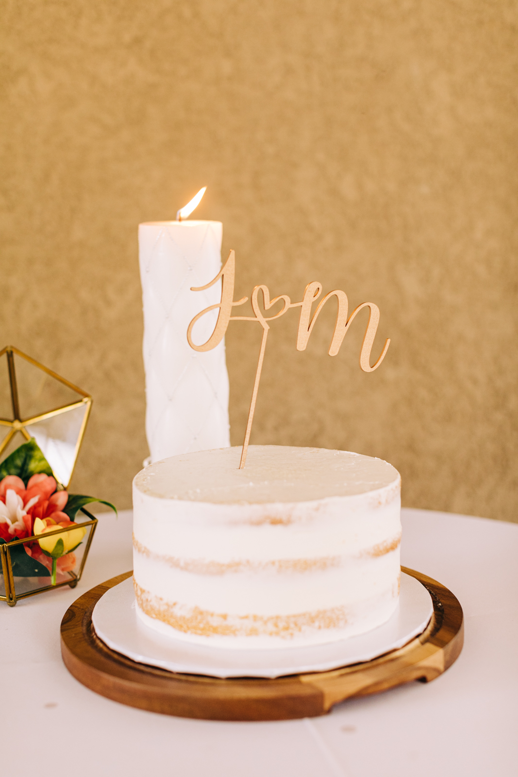 A small naked cake with a candle and a topper for a micro-wedding in Southern California.