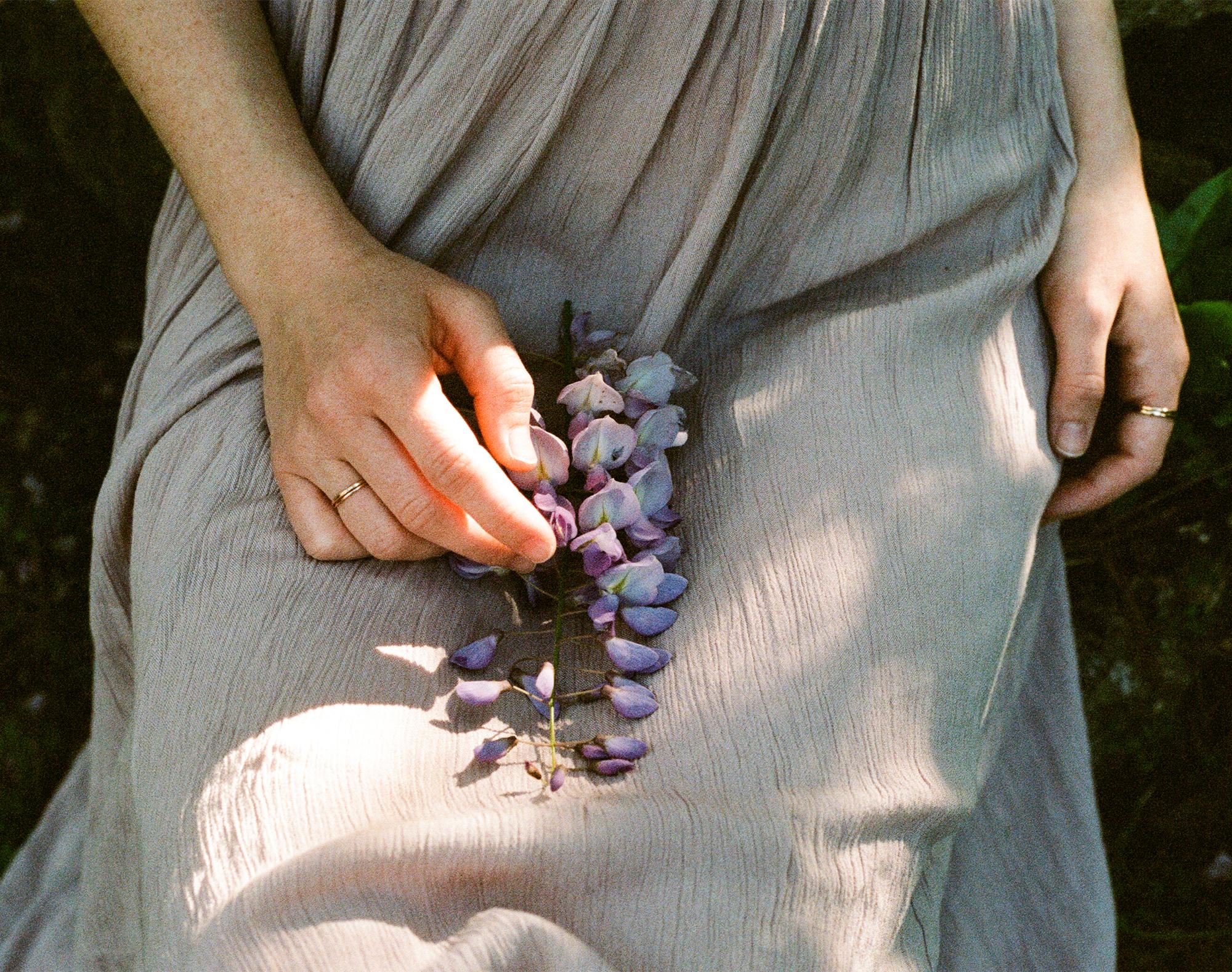 hands of girl holding wisteria shot on 35mm kodak portra 400