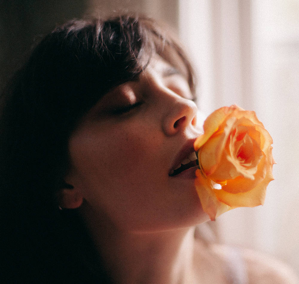 woman with yellow rose in her mouth