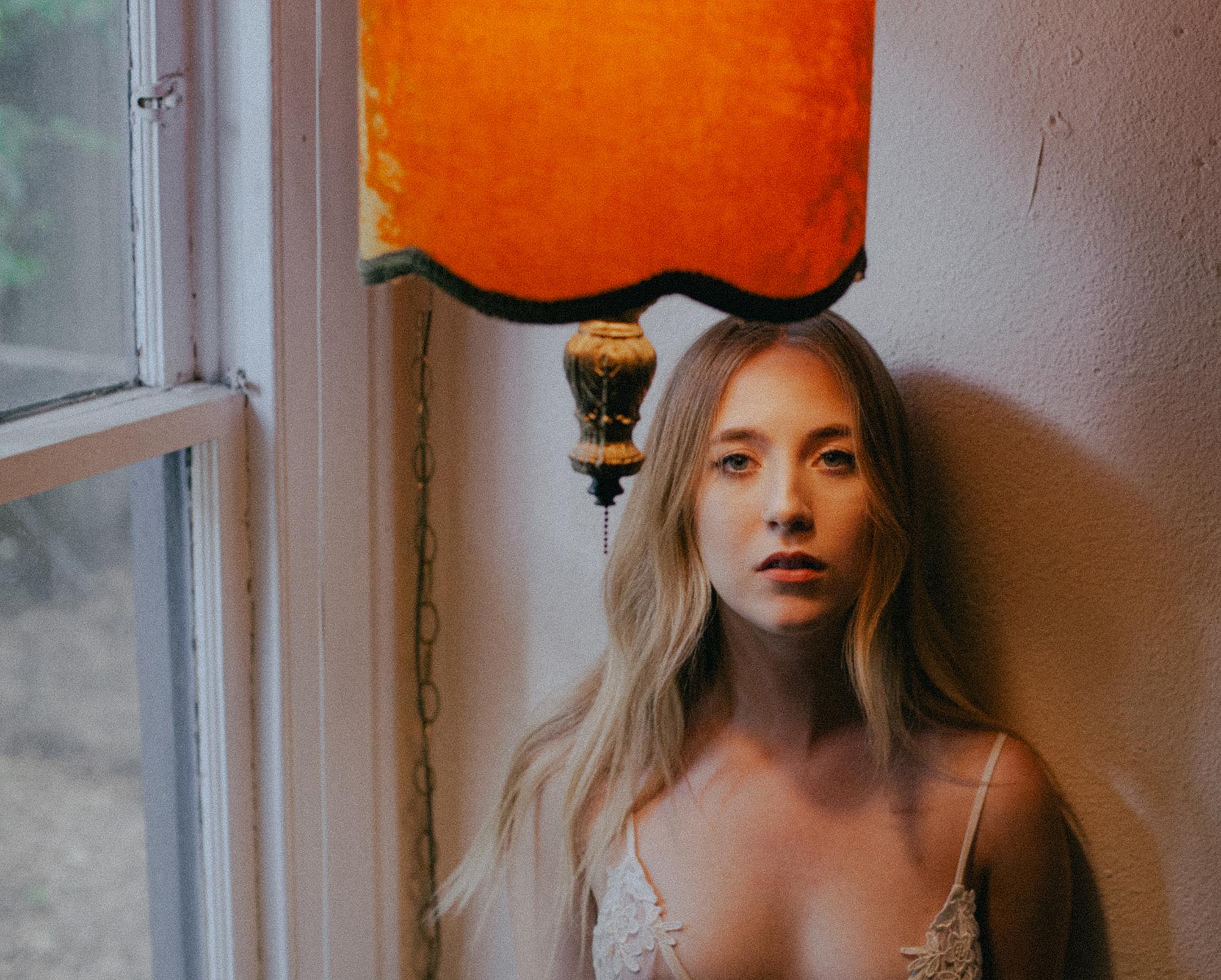 woman in bra under vintage orange lamp