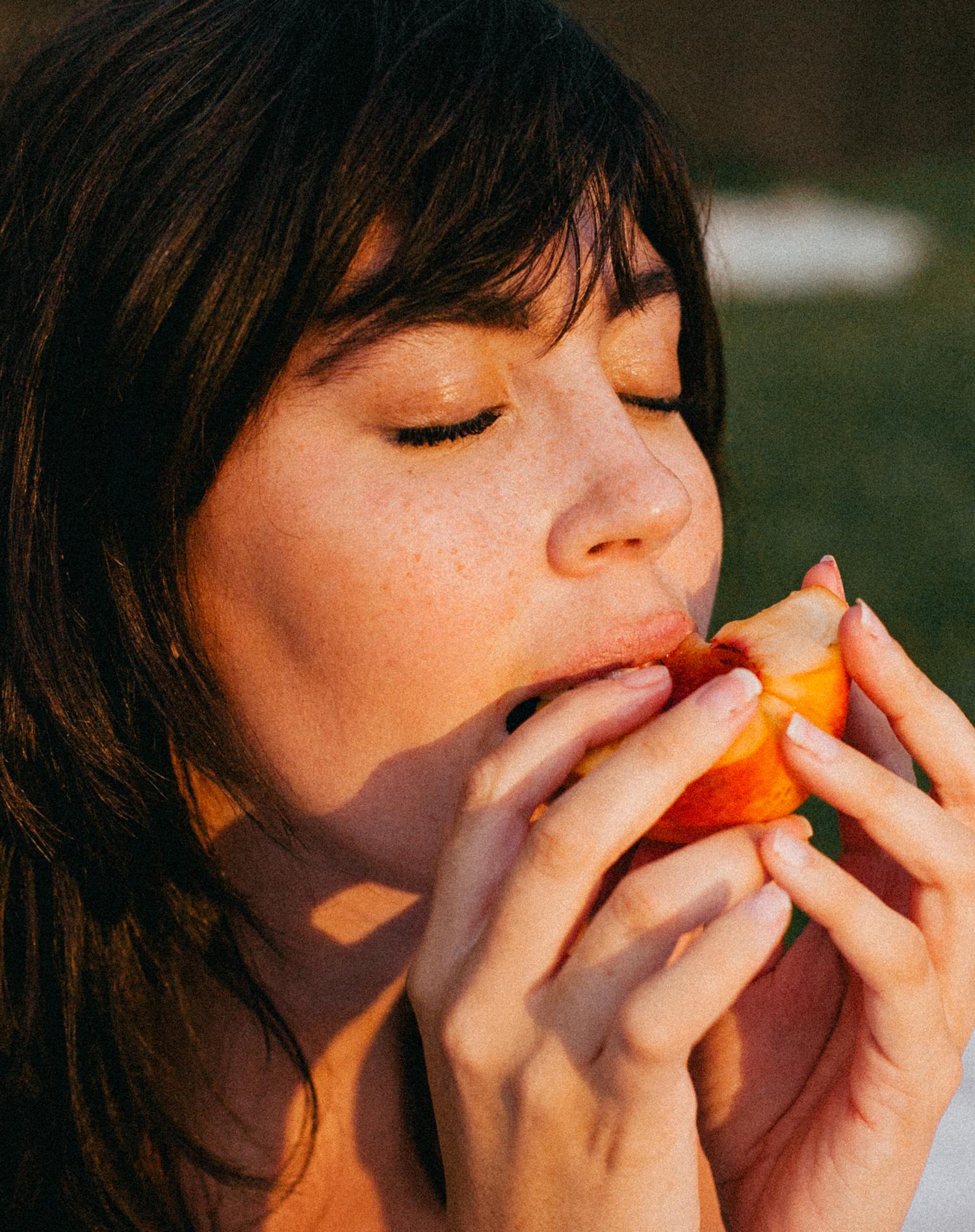 closeup of girl eating peach