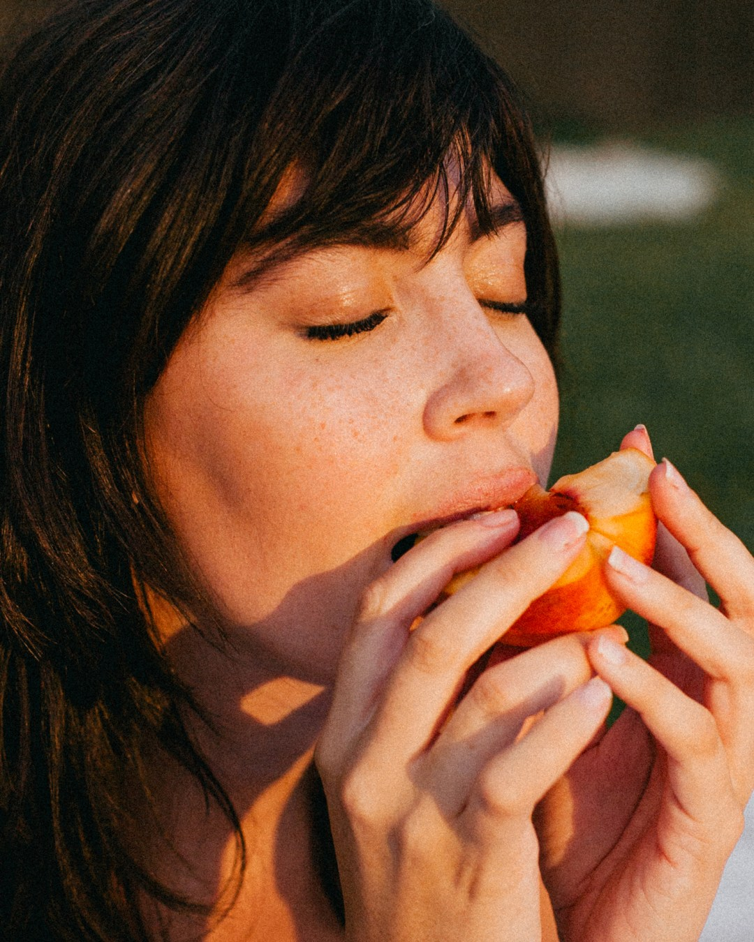 closeup of girl eating peach