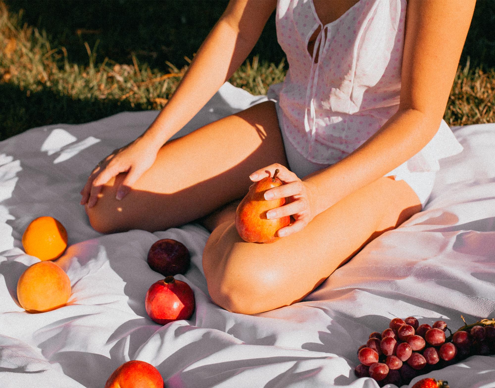 woman on white blanket holding fruit