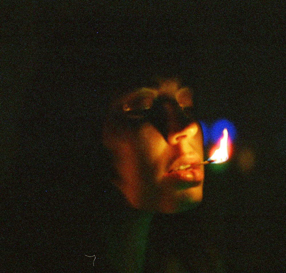 grainy 35mm film of girl with lit matchstick
