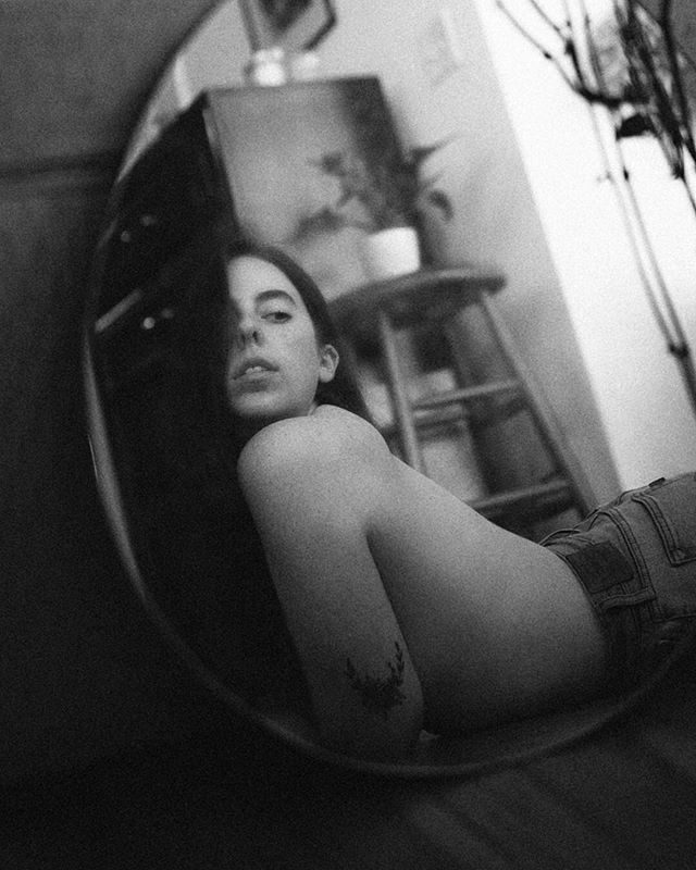 black and white topless woman self portrait in mirror