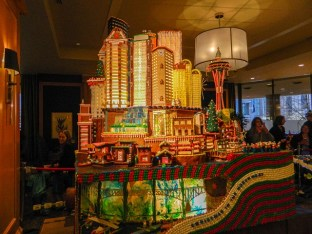 Seattle Gingerbread village: includes iconic buildings like the Space Needle, Columbia Center and Smith Tower, also has a detail of Lake Union with a sea plane and kayakers.