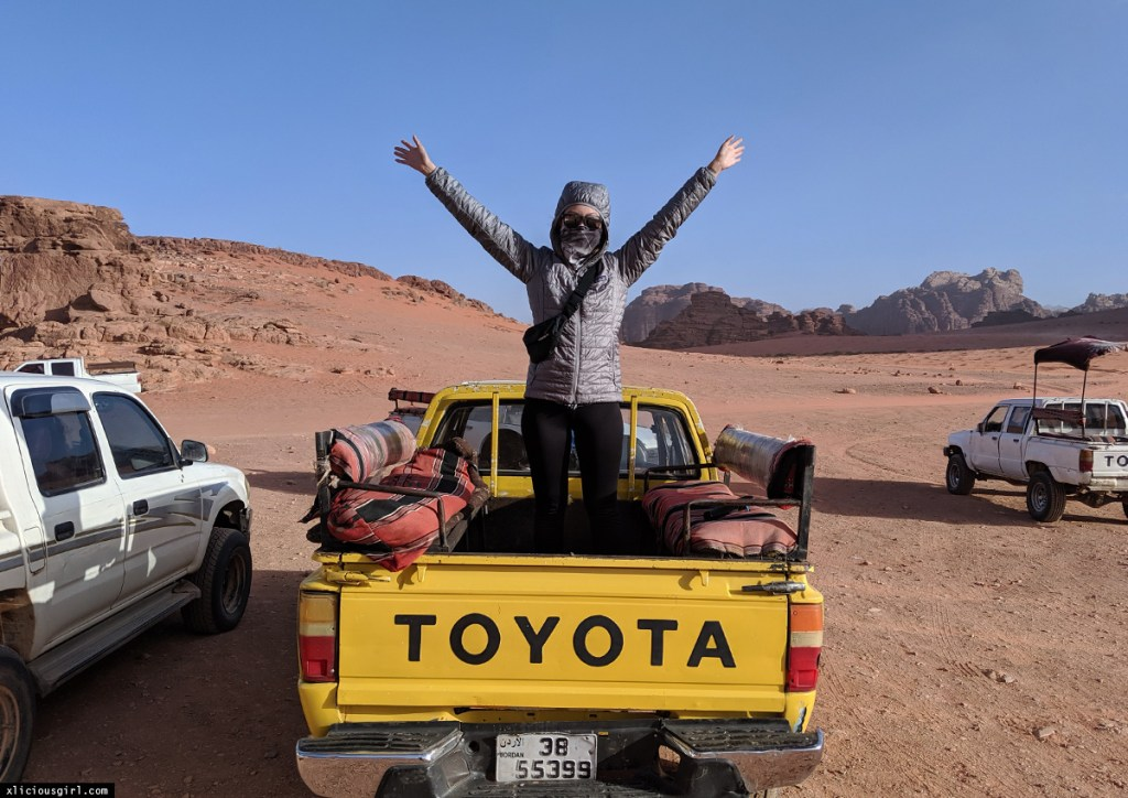 standing on a Toyota truck in the desert