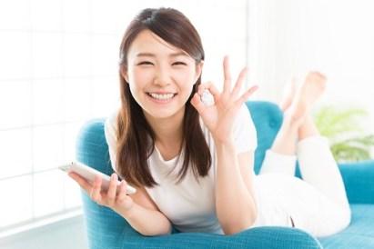 ソファに横になりokマークをする笑顔の女性