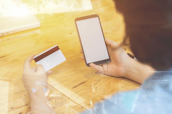 スマートフォン画面でカード払いを行う人