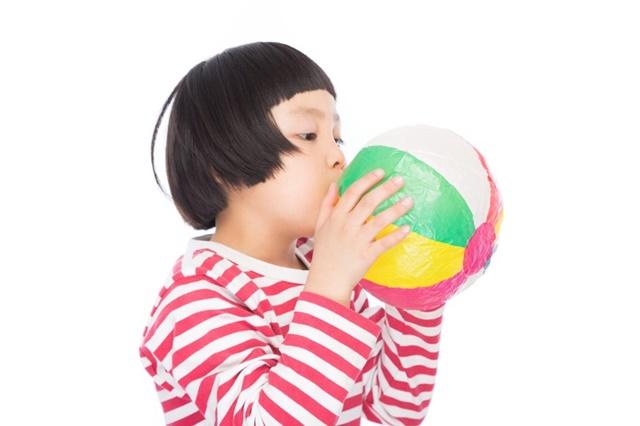 風船を膨らませる女の子