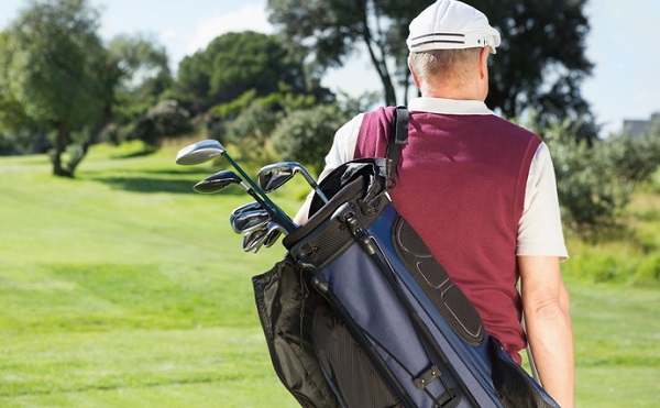 Golfer carrying his golf bag on a sunny day at the golf course
