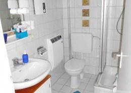 Das weiß geflieste Badezimmer mit Toilette, Duschkabine und Waschtisch mit Unterschrank.