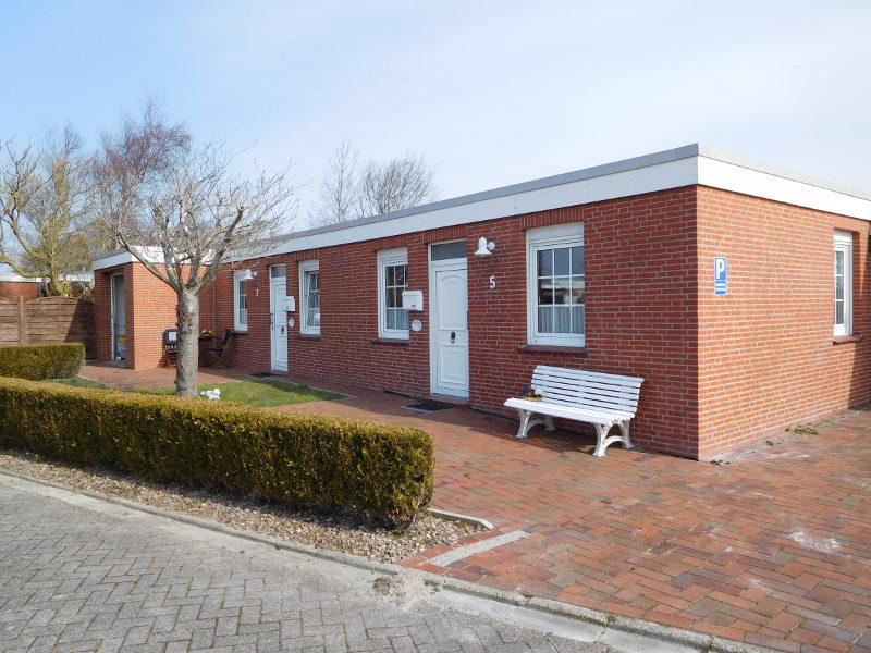 Frontalansicht von Haus Robbenbank 5 mit Eingangstür und Autostellplatz.